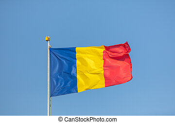 Romania flag waving against clean blue sky, close up