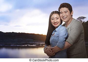Romantic asian couple enjoying sunset