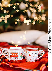 Romantic atmosphere and hot cocoa cups. Holiday lights and red plaid