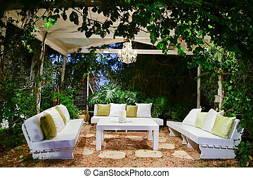 patio romantic in the evening with benches and pillows chandelier and table