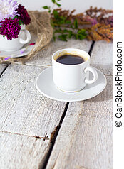 Romantic background with cup of coffee, flowers over white table.
