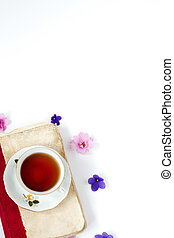 Romantic background with cup of tea ,lilac flowers and retro book over white table .