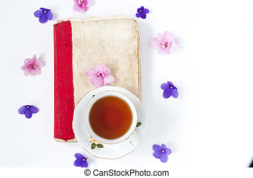 Romantic background with cup of tea lilac flowers and retro book over white table .