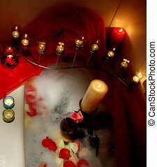 romantic bath - bathtube surrounded with candles, petals and...
