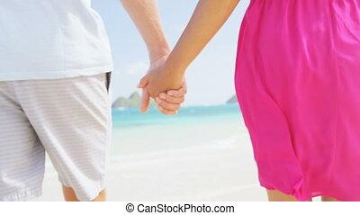 Romantic beach couple in love holding hands on honeymoon. Pink dress, casual beachwear newlywed people standing on travel summer vacations on Lanikai beach, Oahu, Hawaii, USA with Na Mokulua Islands.