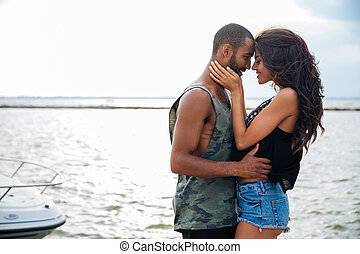 Romantic beautiful couple in love embracing at the pier