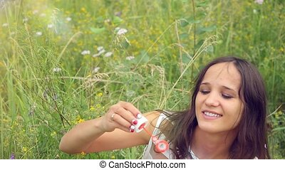 Romantic beautiful young smiles woman blowing soap balloons in a flower meadow