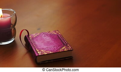 Tracking dolly shot of a candle and a cute little, purple book sitting on a wooden table in a romantic setting.