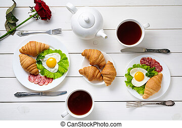 Romantic breakfast for two with heart shaped eggs, salad, croissants, rose flower and black tea on white wooden table background. Food concept of love.