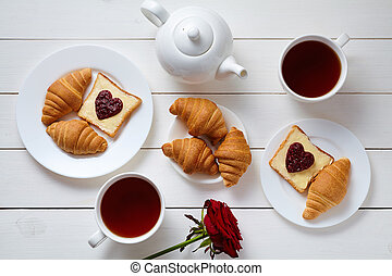 Romantic breakfast for two with toasts, heart shaped jam, croissants, rose and tea on white wooden table background.