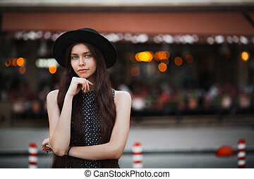 Romantic brunette girl wearing hat and vintage dress posing at the city street on a lights background. Space fir text