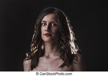 Romantic brunette model in a dark room