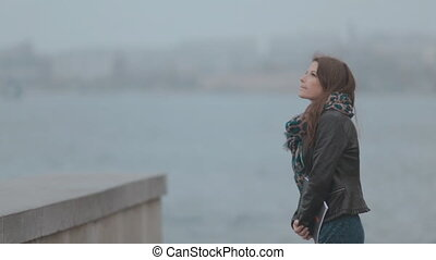 Romantic brunette walks along the seafront with beautiful...