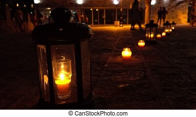 Romantic candle lanterns on the tourist street at night -...