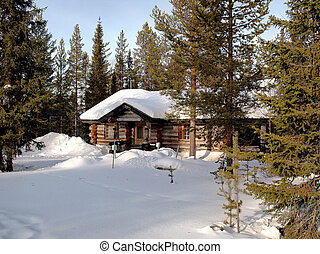 Romantic snow covered log cabin between the trees in a holiday resort in Lapland, Finland.