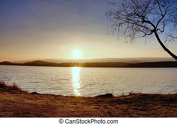 Romantic colorful sunset on the lake. Beach with birch tree and hot red Sun in water mirror