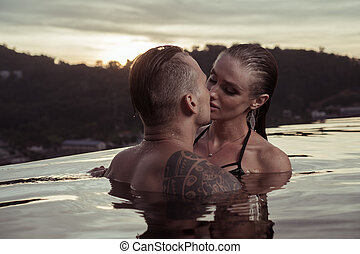 Romantic couple alone in infinity swimming pool