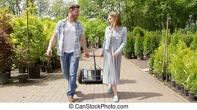 Romantic couple carrying flowerpot in garden - Beautiful...