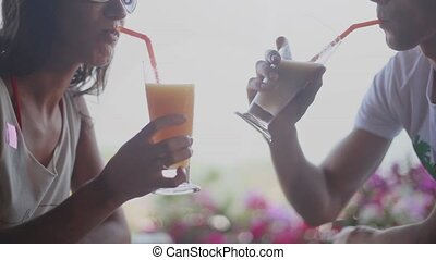 Romantic couple drinking tropical cocktails in an outdoor cafe. 1920x1080