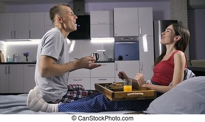 Romantic couple eating breakfast in bed - Young beautiful...