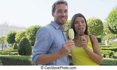 Romantic couple eating ice cream at park. Woman and man eating ice cream bar on stick biting looking happy at camera outdoor in summer. RED EPIC SLOW MOTION.