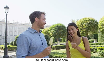 Romantic couple eating ice cream at park. Woman and man eating ice cream bar on stick laughing happy on date talking outdoor in summer. Madrid, Spain. Shot on RED EPIC in SLOW MOTION.