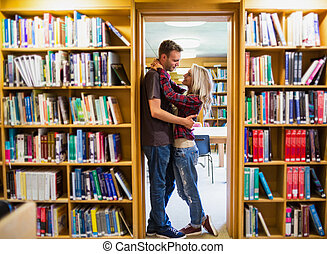 Romantic couple embracing by bookshelf - Full length side...