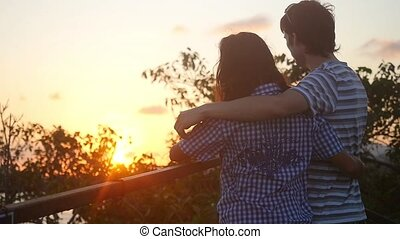 Romantic couple embracing enjoying watching the sunset hugging shoulders romance date harmony in slow motion.