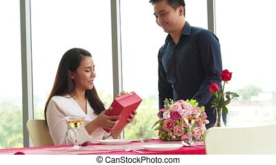 Romantic couple giving gift to lover at restaurant . Happy couple lifestyle .