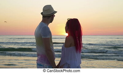 Romantic couple holding hands and looking at the horizon on the beach at sunset
