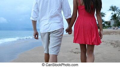 Romantic couple holding hands walking on beach in elegant ...