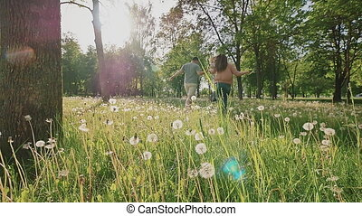 Romantic couple in a beautiful green park with lots of trees and white dandelions in the sunlight. They run, hugging each other and whirling together. Summer. Love. Recreation.