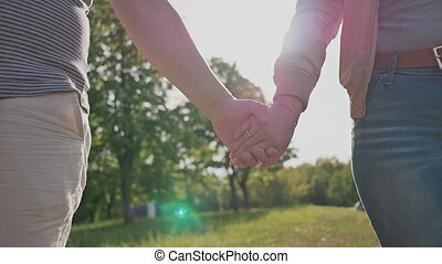 Romantic couple in a green summer park. They hold each other's hand in the rays of sunlight. Close-up.