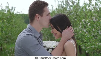 Closeup of happy mixed race couple standing close to each other touching foreheads among flowering apple trees. Loving man kissing woman on forehead, young bride and groom enjoying tenderness and love