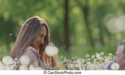 Romantic couple in summer on a clearing among white dandelions. They joyfully blow and spray dandelions. They fall into the grass. Happy together. Summer.