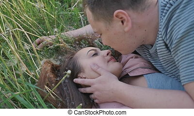 Romantic couple in summer on a glade. The girl lies in the grass among white dandelions. The guy touches the girl's hair. In the hair there are dandelions. Happy together. Summer. The sun.