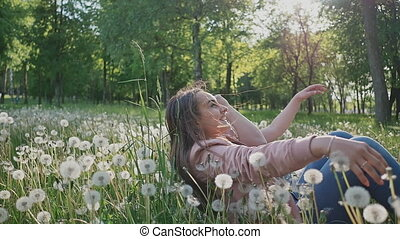 Romantic couple in summer on a glade. They fall into the grass with white dandelions. Happy together. Summer. The sun.