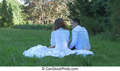 Romantic couple in white clothes embrace and kiss on date. They are sitting on the green grass in a beautiful park.