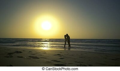 Romantic couple is falling in love on the beach in water. Man with woman is holding hands and walking along the golden sandy beach. Two hipster in love, walks, relaxes at amazing beautilful sunset