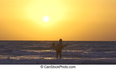 Romantic couple is falling in love on the beach at sunset, kiss each other. Happy Young man is circling the girl in his arms on the shore of sea in water. Two people in love, have fun under the sun.