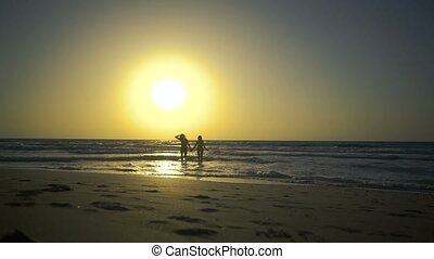 Romantic couple is falling in love on the beach in water. Man with woman is holding hands and walking along the golden sandy beach. Two hipster in love, walks, relaxes at amazing beautilful sunset.
