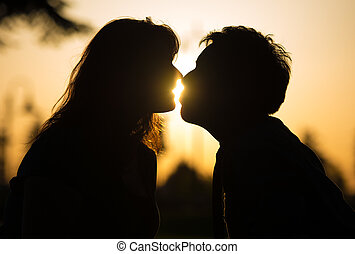 Sensual portrait of the profile in silhouette of a romantic couple kissing at sunset with sun flare between their lips