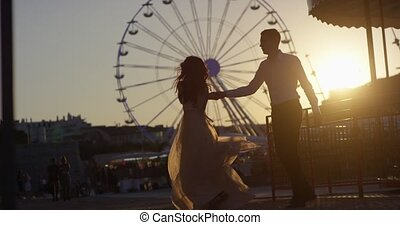Romantic couple kissing, dancing, going crazy on the sunset in the park near Ferris Wheel, Nice, France. Shot in slow motion 4k
