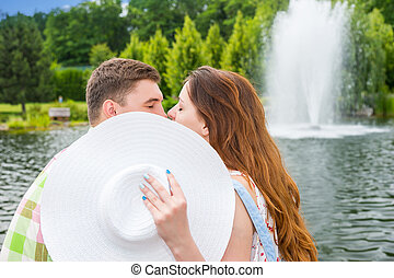 Romantic couple kissing hiding behind the hat