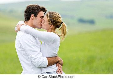 romantic couple kissing on grassland