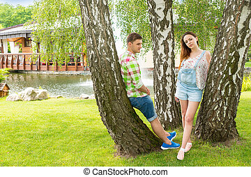 Romantic couple leaning on trees in a park with beautiful background