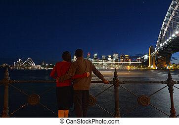 Romantic couple looks at Sydney skyline at dusk