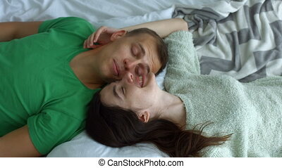 Portrait of romantic couple in love lying on bed face to face and bonding while spending leisure together at home. Top view. Affectionate couple chatting while lying on bed in opposite direction.