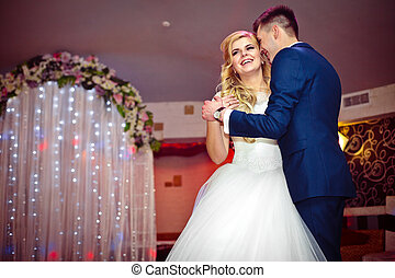 Romantic couple of newlyweds first elegant dance at wedding reception hall