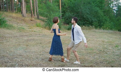 Romantic couple of young people are embracing a clearing in the summer forest.